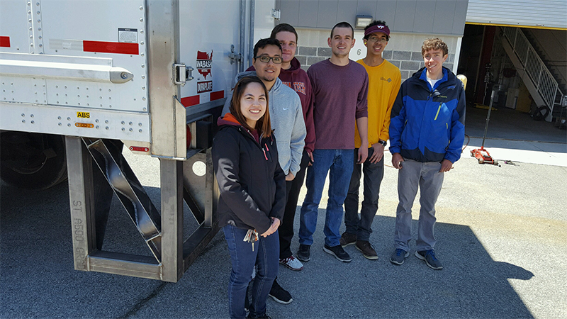 Senior design team members Kristine Adriano, Daniel Carrasco, Andrew Pitt, Wayne Carter, Brian Smith, and Sean Gardner pose with a bumper designed to limit damage to vehicles under-riding the back of tractor trailers.